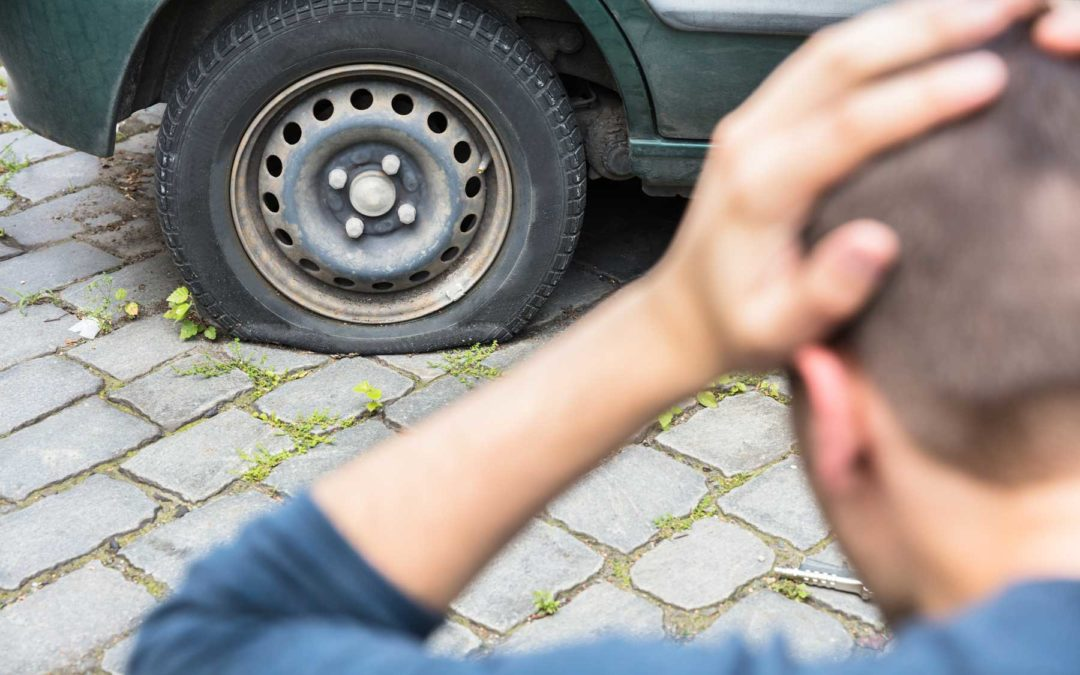 Man looking at a flat tire with his hands on his head